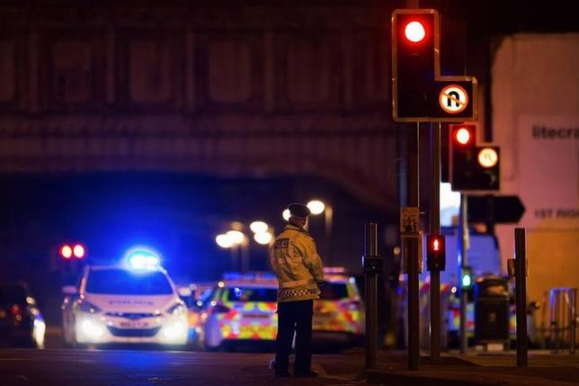 Police vehicles and a police officer are seen outside the Manchester Arena, where U.S. singer Ariana Grande had been performing in Manchester, northern England, Britain May 22, 2017. REUTERS/Jon Super