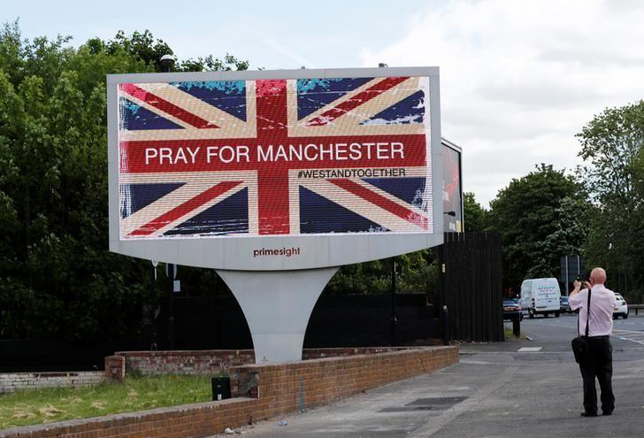 A man photographs a sign in Manchester, Britain May 23, 2017. REUTERS/Stefan Wermuth