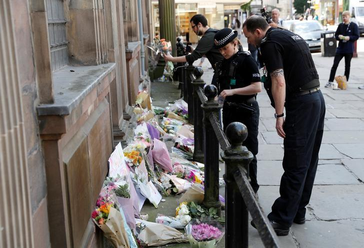 Police officers look at flowers and messages left for the victims of the Manchester Arena attack, in central Manchester, Britain May 23, 2017. REUTERS/Darren Staples