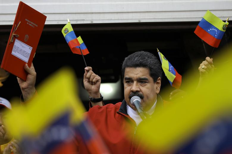Venezuela's President Nicolas Maduro holds a document with the details of a ''constituent assembly'' to reform the constitution during a rally at Miraflores Palace in Caracas, Venezuela May 23, 2017. REUTERS/Carlos Barria