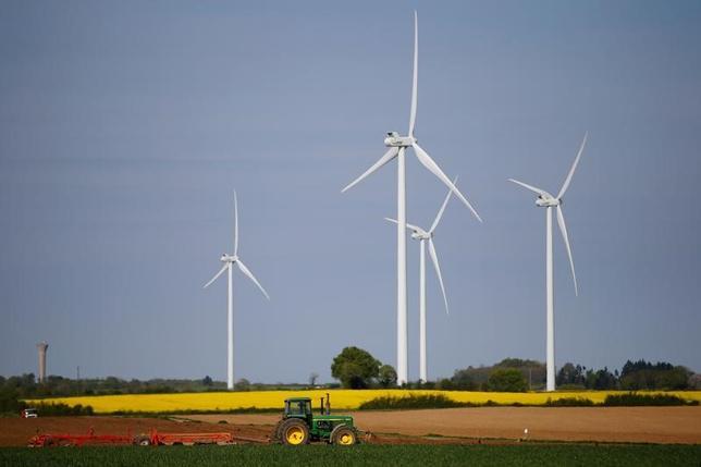 5月23日、経済協力開発機構(OECD)は、主要20カ国(G20)が地球温暖化対策に取り組んだ場合、現行政策を継続した場合と比べて2050年時点で約5%成長を押し上げる効果が得られるとする報告書を公表した。写真は発電用の風車。フランスのパンプルーで4月撮影(2017年 ロイター/Stephane Mahe)