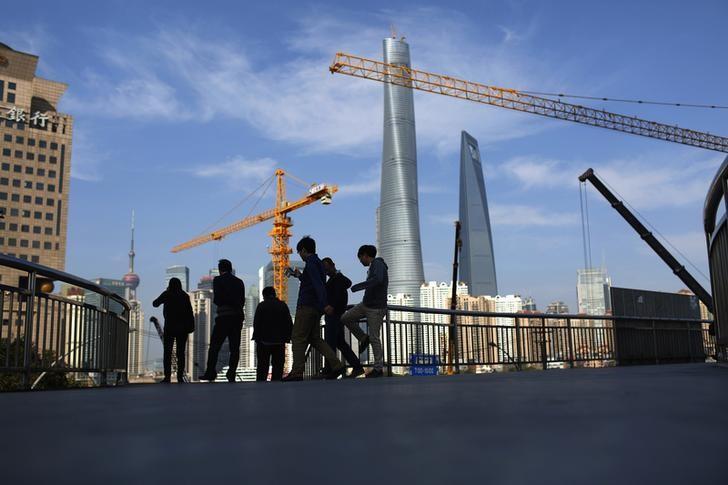 资料图片:2014年11月,上海浦东陆家嘴金融区,行人经过一座过街桥。REUTERS/Aly Song