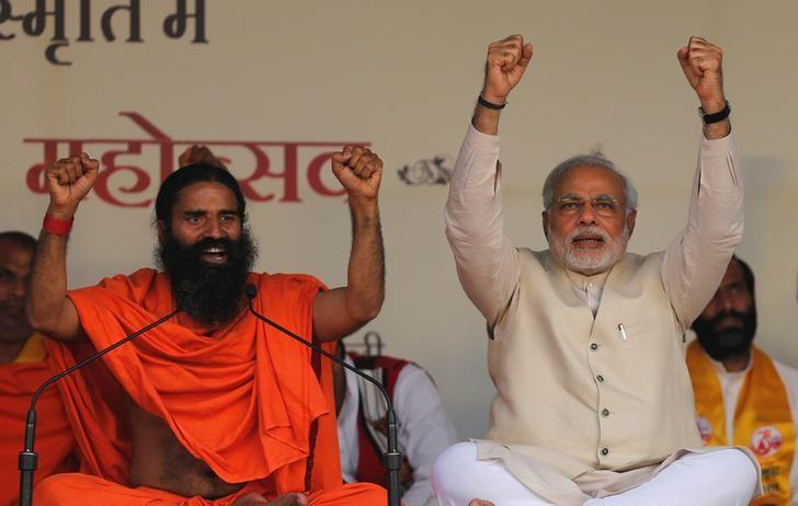 FILE PHOTO: Hindu nationalist Narendra Modi, prime ministerial candidate for India's main opposition Bharatiya Janata Party (BJP) and Indian yoga guru Baba Ramdev (L) raise their hands as they chant patriotic slogans during a Yoga Mahotsav or festival, in New Delhi March 23, 2014.  To match Special Report INDIA-MODI/RAMDEV  REUTERS/Adnan Abidi