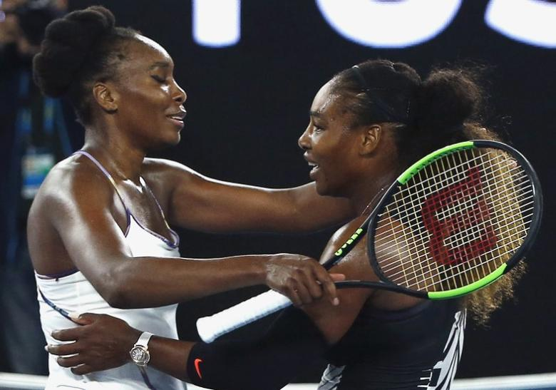 FILE PHOTO: Tennis - Australian Open - Melbourne Park, Melbourne, Australia - 28/1/17 Serena Williams of the U.S. hugs Venus Williams of the U.S. after winning her Women's singles final match. REUTERS/Thomas Peter