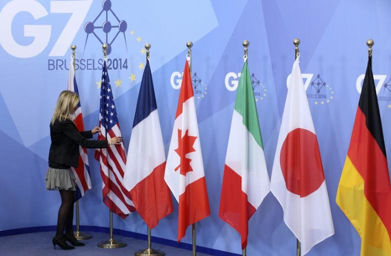 FILE PHOTO: An official adjusts flags during the G7 summit at the European Council building in Brussels June 5, 2014.    REUTERS/Francois Lenoir
