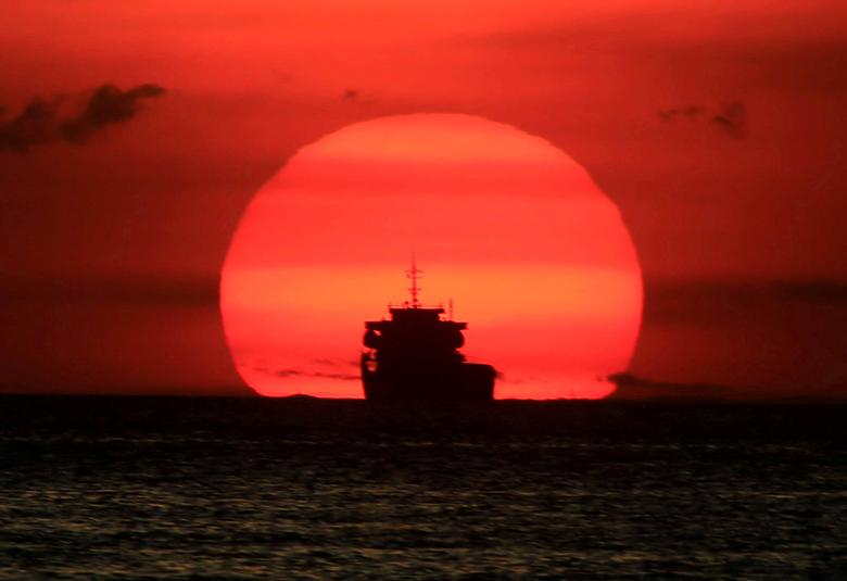 FILE PHOTO: A cargo ship is silhouetted as the sun sets along the coast of Manila bay in Metro Manila, Philippines January 27, 2017. REUTERS/Romeo Ranoco/File Photo