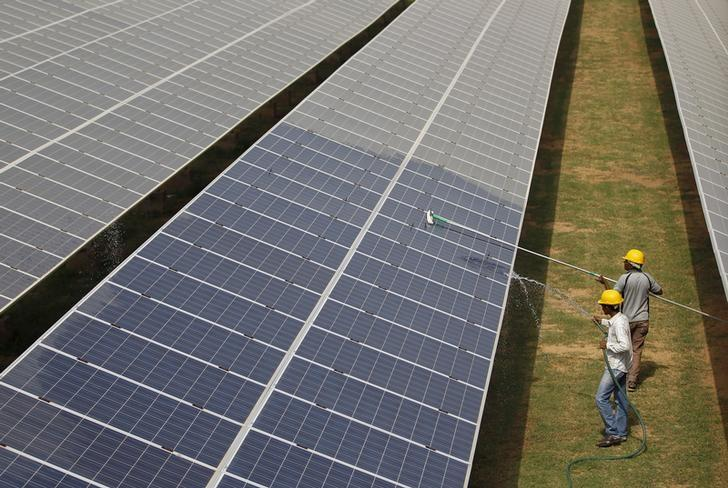 Workers clean photovoltaic panels inside a solar power plant in Gujarat, India, July 2, 2015. REUTERS/Amit Dave/Files