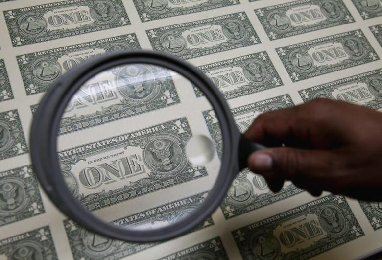 United States one dollar bills are inspected under a magnifying glass during production at the Bureau of Engraving and Printing in Washington November 14, 2014.   REUTERS/Gary Cameron