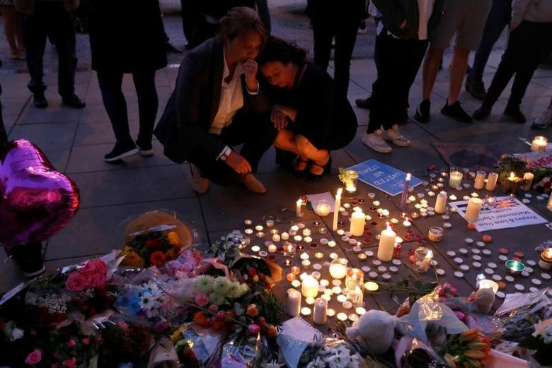 Women pay their respects to all those affected by the bomb attack, following a vigil in central Manchester, Britain May 23, 2017.  REUTERS/Peter Nicholls