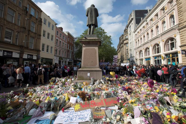 Messages and floral tributes left for the victims of the attack on Manchester Arena lie around the statue in St Ann's Square in central Manchester. REUTERS/Jon Super