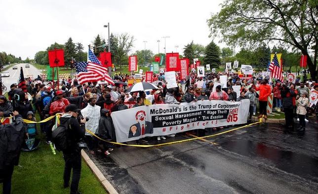 5月24日、米ファストフード大手マクドナルドの店舗で働く従業員ら数百人が、年次株主総会が開催される中、イリノイ州オークブルック(シカゴ郊外)の同社本社前で賃上げを求めてデモを行った(2017年 ロイター/Frank Polich)