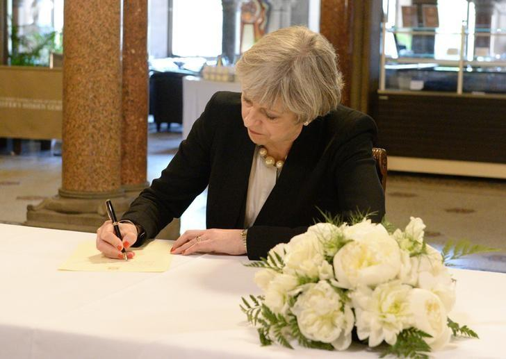 Britain's Prime Minister Theresa May writes a message for the book of condolences for the victims of the attack on Manchester Arena, at Manchester Town Hall in Manchester May 23, 2017. REUTERS/Ben Birchall/Pool