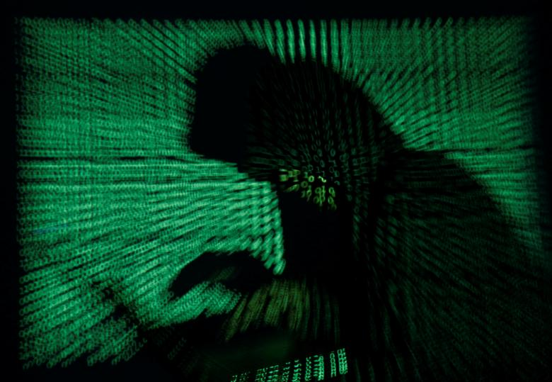 A hooded man holds a laptop computer as cyber code is projected on him in this illustration picture taken on May 13, 2017.  REUTERS/Kacper Pempel/Illustration