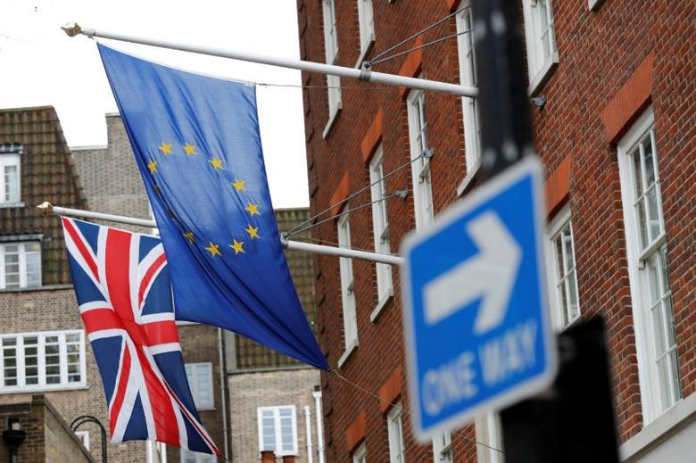 A traffic sign is seen in front of European and Union flags in London, Britain, March 20, 2017. REUTERS/Stefan Wermuth