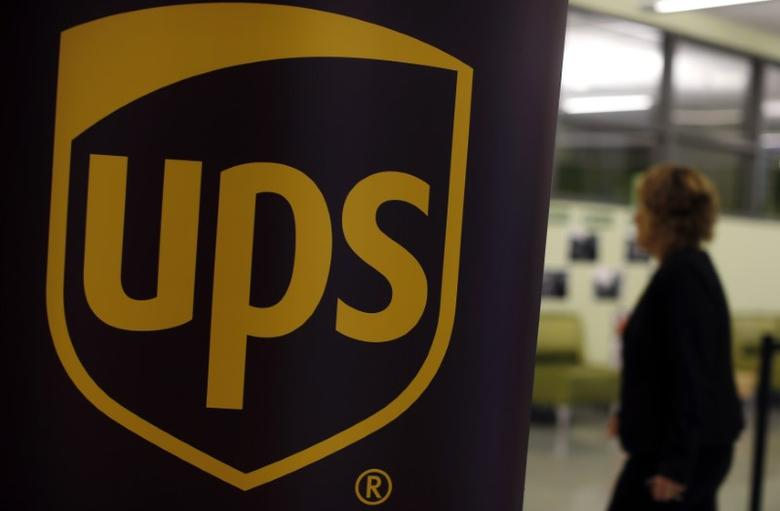 FILE PHOTO: A woman walks past a sign bearing the logo of United Parcel Service (UPS) in Chicago, Illinois, October 18, 2014.  REUTERS/Jim Young