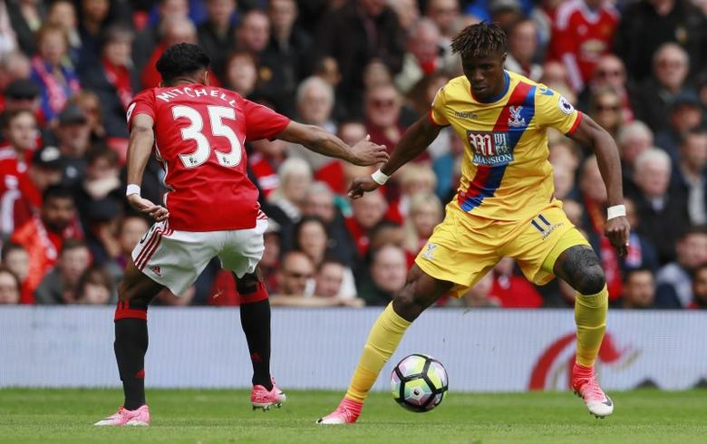 Britain Football Soccer - Manchester United v Crystal Palace - Premier League - Old Trafford - 21/5/17 Crystal Palace's Wilfried Zaha in action with Manchester United's Demetri Mitchell Action Images via Reuters / Jason Cairnduff Livepic
