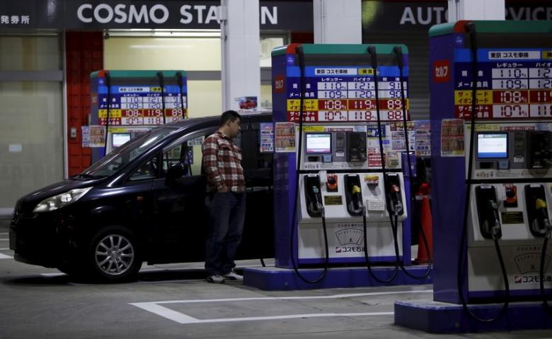 资料图片:2015年12月,东京,一名顾客在Cosmo能源控股旗下加油站等待给车辆加油。REUTERS/Yuya Shino
