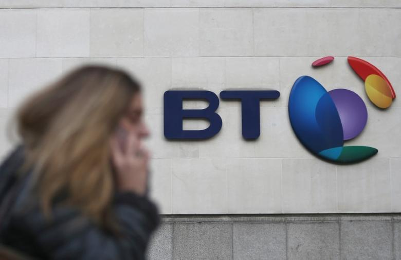 A woman talks on her phone as she passes a branded sign displayed outside of a BT building in London, Britain January 27, 2017. REUTERS/Neil Hall