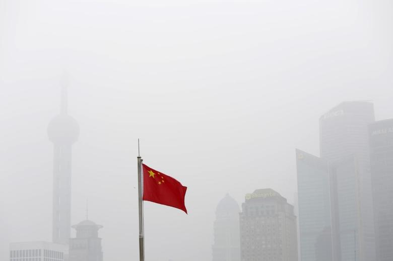 Chinese flag is seen in front of the financial district of Pudong amid heavy smog in Shanghai, China, December 23, 2015. REUTERS/Aly Song