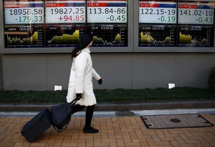 A woman walks past electronic board showing stock prices and Japanese Yen's exchange rate outside a brokerage at a business district in Tokyo, Japan, January 23, 2017.  REUTERS/Kim Kyung-Hoon