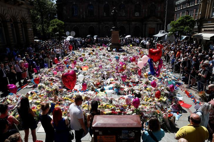 People look at tributes to the victims of the attack on the Manchester Arena, in central Manchester, Britain May 26, 2017. REUTERS/Stefan Wermuth