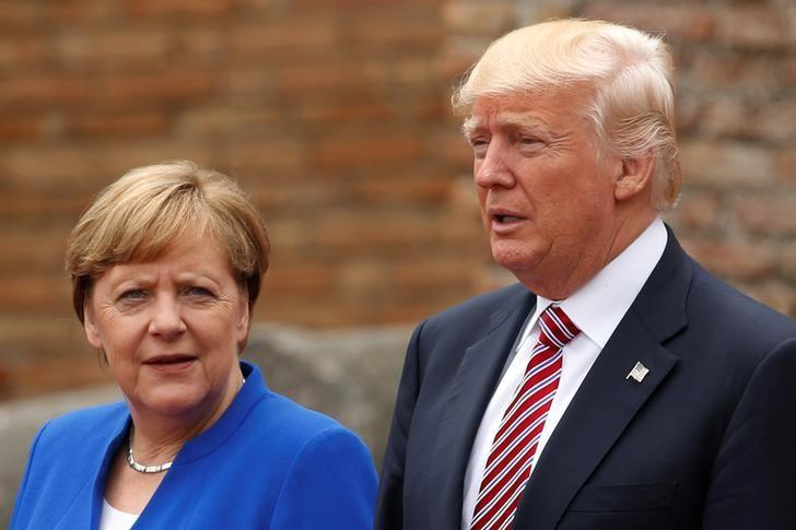 U.S. President Donald Trump and German Chancellor Angela Merkel pose during a family phto at the Greek Theatre during a G7 summit in Taormina, Sicily, Italy, May 26, 2017. REUTERS/Jonathan Ernst
