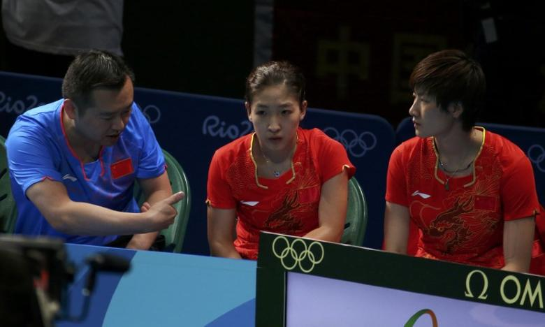 Women's Team - Gold Medal Match - Riocentro - Pavilion 3 - Rio de Janeiro, Brazil - 16/08/2016. Liu Shiwen (CHN) of China and Ding Ning (CHN) of China sit with their coach Kong Linghui before playing their doubles match against Petrissa Solja (GER) of Germany and Xiao Na Shan (GER) of Germany.     REUTERS/Jeremy Lee
