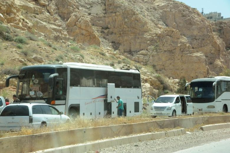 FILE PHOTO - A view shows a convoy of buses carrying rebel fighters and their relatives from the besieged Damascus district of Barzeh, in this handout picture provided by SANA on May 8, 2017, Syria. SANA/Handout via REUTERS