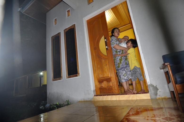 A woman and children stand in the doorway of a house during an earthquake in Palu, Central Sulawesi, Indonesia May 29, 2017 in this photo taken by Antara Foto. Antara Foto/Mohamad Hamzah/via REUTERS