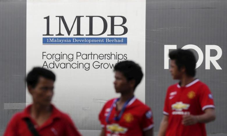FILE PHOTO: Men walk past a 1 Malaysia Development Berhad (1MDB) billboard at the fund's flagship Tun Razak Exchange development in Kuala Lumpur March 1, 2015.   REUTERS/Olivia Harris/File Photo
