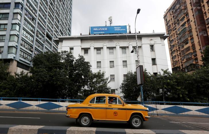 A taxi drives past a Reliance Communications Ltd., controlled by billionaire Anil Ambani, office building in Kolkata, India, September 9, 2016.  REUTERS/Rupak De Chowdhuri/File Photo