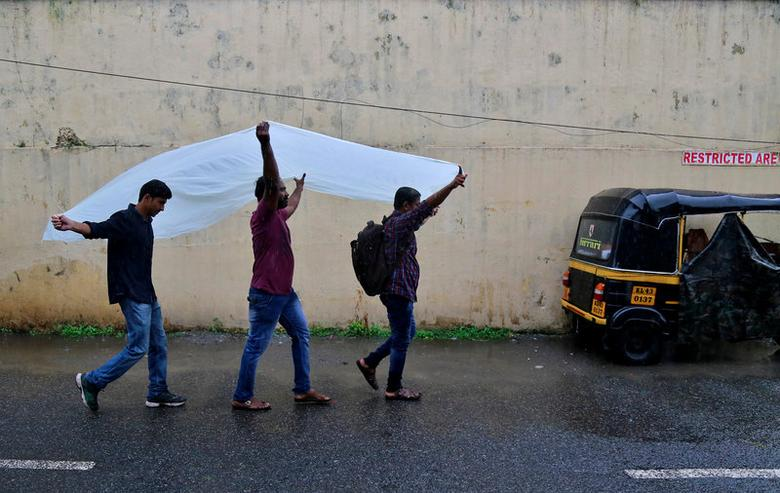 Men use a plastic sheet to cover from rain as they walk along a road in Kochi, India, May 30, 2017. REUTERS/Sivaram V