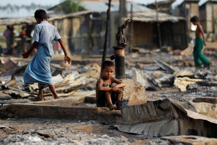 FILE PHOTO: A boy sit in a burnt area after fire destroyed shelters at a camp for internally displaced Rohingya Muslims in the western Rakhine State near Sittwe, Myanmar May 3, 2016. REUTERS/Soe Zeya Tun/File Photo