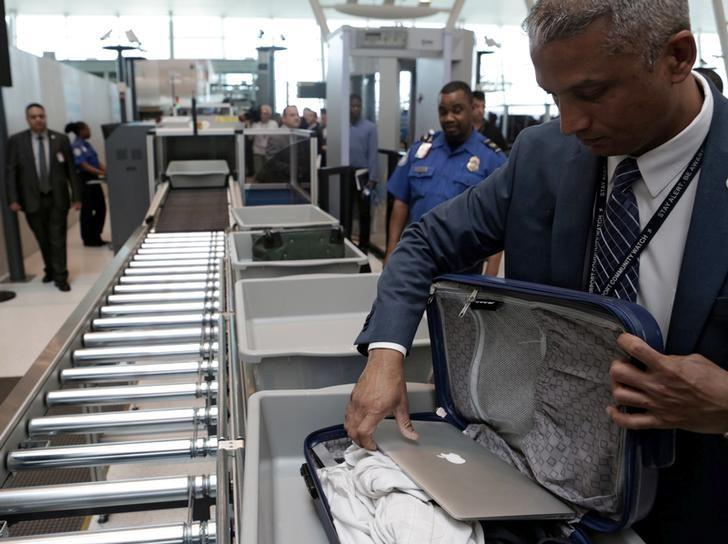 A TSA official removes a laptop from a bag for scanning using the Transport Security Administration's new Automated Screening Lane technology at Terminal 4 of JFK airport in New York City, U.S., May 17, 2017. REUTERS/Joe Penney/Files