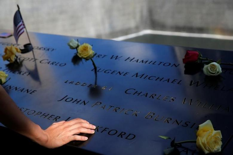 A person touches the south reflecting pool at the National September 11 Memorial and Museum on the 15th anniversary of the 9/11 attacks in Manhattan, New York, U.S., September 11, 2016.  REUTERS/Andrew Kelly -