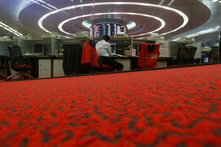 FILE PHOTO - A floor trader monitors share prices during afternoon trading at the Hong Kong Stock Exchange in Hong Kong, China September 26, 2016.    REUTERS/Bobby Yip/File Photo