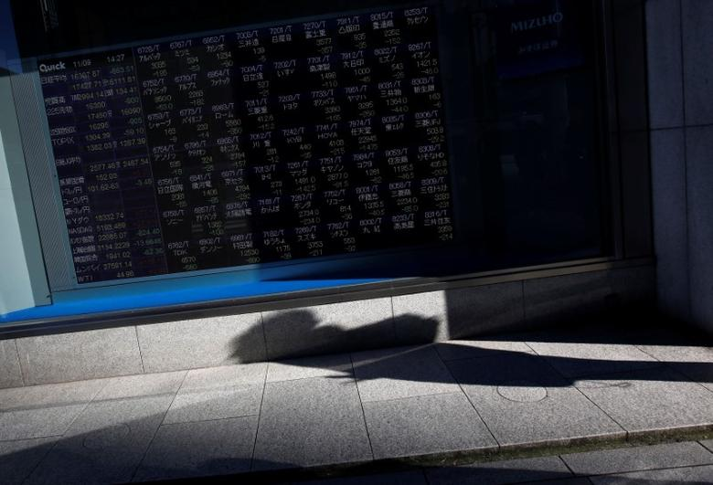 A pedestrian casts a shadow in front of an electronic stock quotation board outside a brokerage in Tokyo, Japan, November 9, 2016. REUTERS/Issei Kato