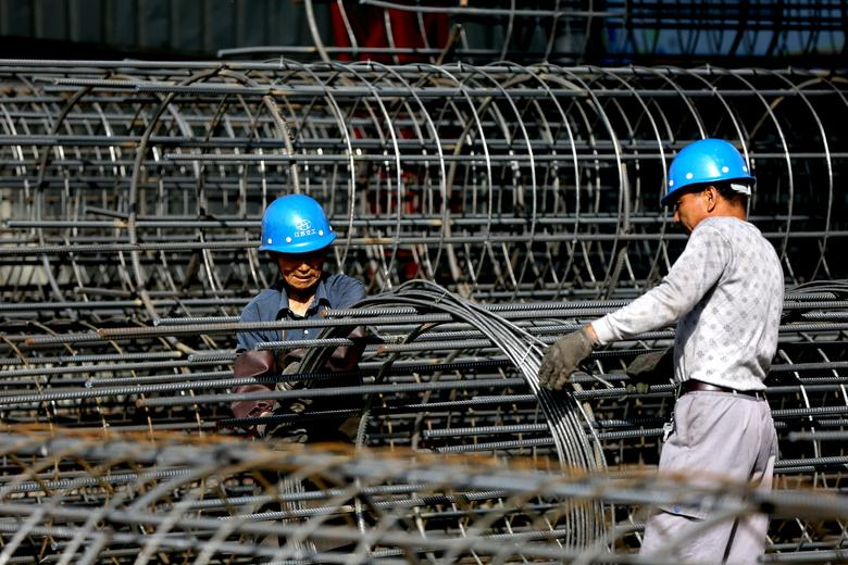 FILE PHOTO: Workers make steel cages at a construction site in Huai'an, Jiangsu province, China May 14, 2017. REUTERS/Stringer