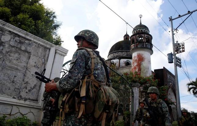 5月30日、フィリピン南部ミンダナオ島のマラウィ市で過激派組織「イスラム国(IS)」を支持する武装勢力と政府軍による衝突が続いている問題で、フィリピンの情報関係筋は、海外から戦闘員が流入し闘争に加わっていると指摘した。写真は同市のモスクの近くで警備にあたるフィリピン海軍の兵士ら(2017年 ロイター/Erik De Castro)