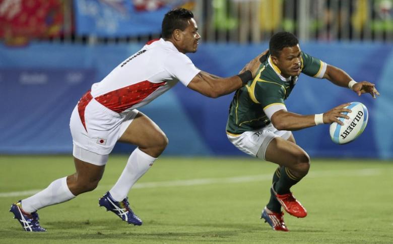 FILE PHOTO: 2016 Rio Olympics - Rugby -  Men's Bronze Medal Match - Japan v South Africa - Deodoro Stadium - Rio de Janeiro, Brazil - 11/08/2016. Juan de Jongh (RSA) of South Africa scores ahead of Lomano Lava Lemeki (NZL) of Japan. REUTERS/Phil Noble