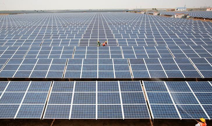 Workers install photovoltaic solar panels at the Gujarat Solar Park under construction in Charanka Village in Patan district of Gujarat April 14, 2012. REUTERS/Amit Dave/Files