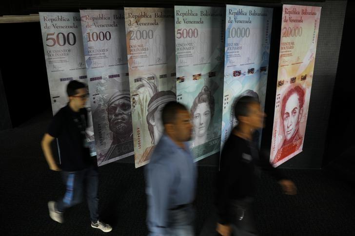 People walk by banners of Venezuelan bolivar notes displayed at the Venezuelan Central Bank building in Caracas, Venezuela May 23, 2017. REUTERS/Carlos Barria
