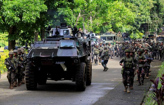 An armored personnel carrier and government troops prior to the assault. REUTERS/Romeo Ranoco