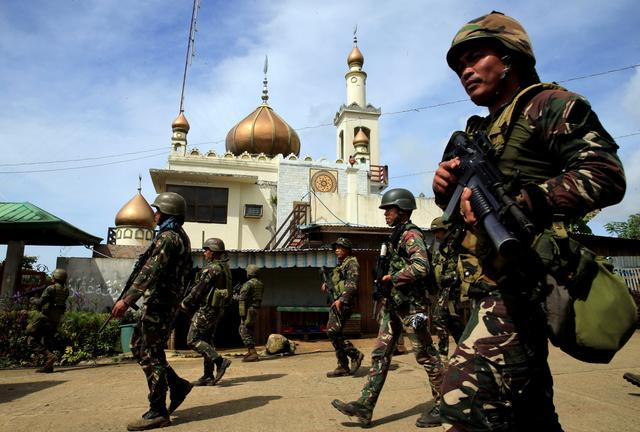 Government troops walk past a mosque before their assault. REUTERS/Romeo Ranoco