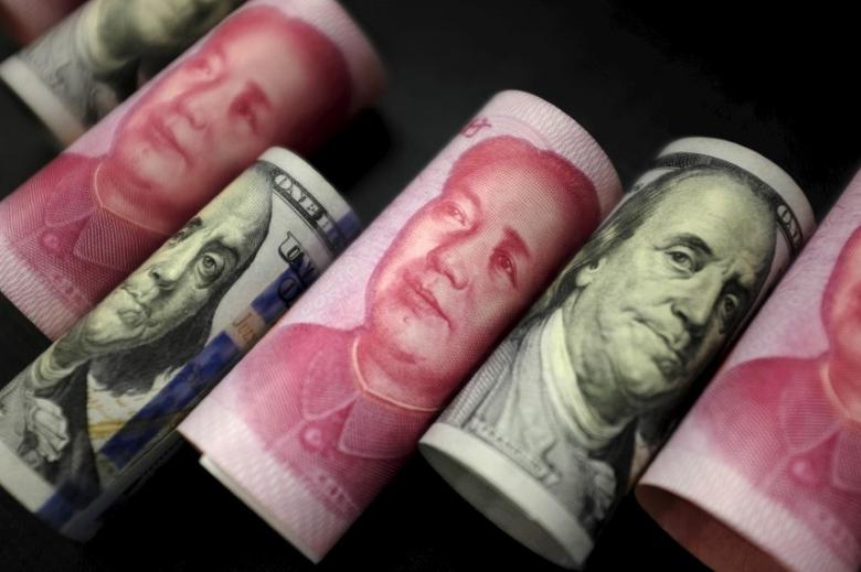 资料图片:2016年1月,美元和人民币纸币。REUTERS/Jason Lee
