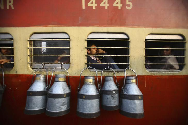 Empty milk containers hang from the window of a train in Uttar Pradesh November 10, 2012. REUTERS/Navesh Chitrakar/Files
