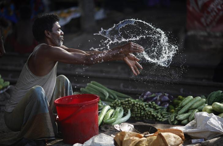 A vendor splashes water as he sells vegetable next to a railway track in Dhaka May 29, 2014.  REUTERS/Andrew Biraj/Files