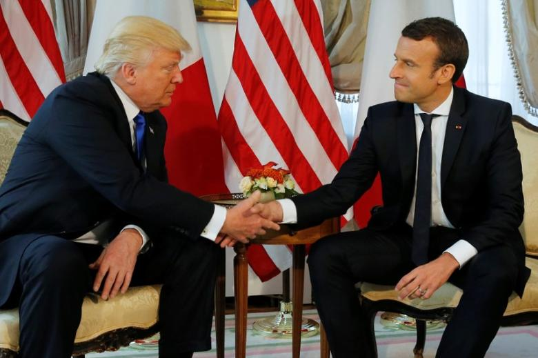 FILE PHOTO: U.S. President Donald Trump (L) and French President Emmanuel Macron shake hands before a working lunch ahead of a NATO Summit in Brussels, Belgium, May 25, 2017.  REUTERS/Jonathan Ernst