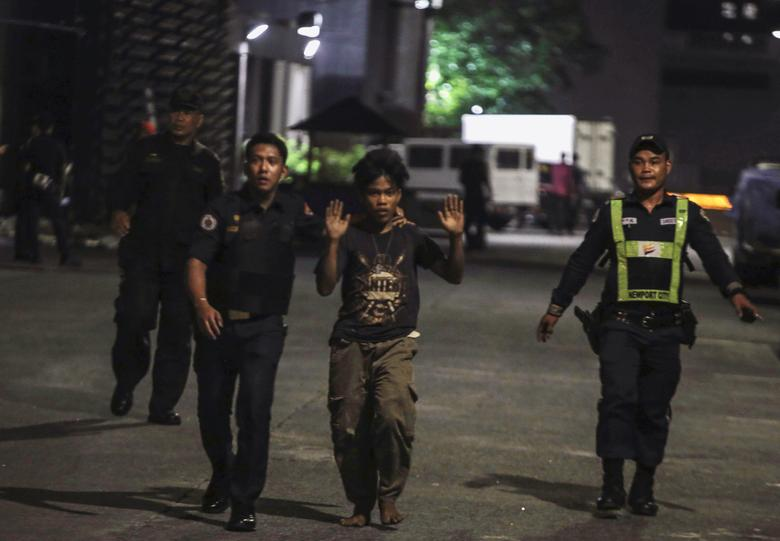Policemen and a security guard escorting a hotel worker is seen at the entrance of a hotel after a shooting incident inside Resorts World Manila in Pasay City, Metro Manila, Philippines June 2, 2017. REUTERS/Stringer