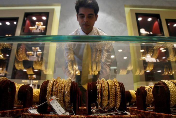 A salesman arranges gold bangles in a display case inside a jewellery showroom on the occasion of Akshaya Tritiya, a major gold buying festival, in Agartala, India, April 28, 2017. REUTERS/Jayanta Dey/File Photo